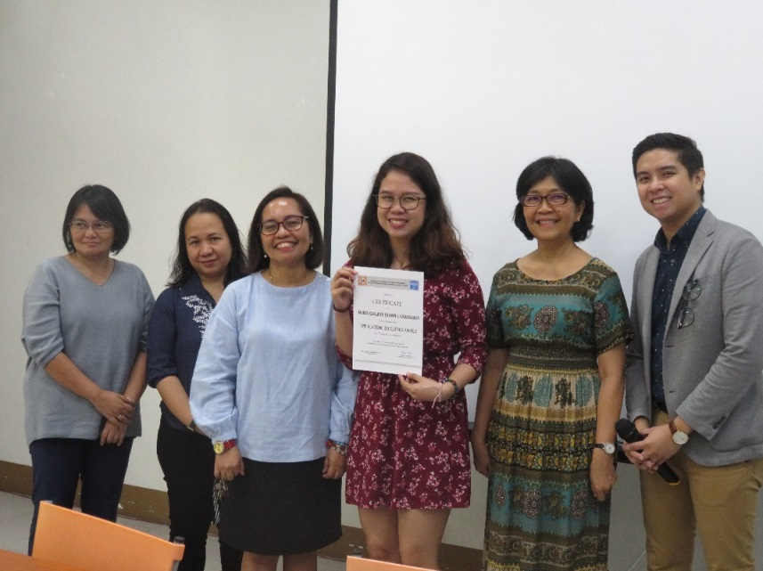Ms. Cabaraban beams as she holds her certificate. Flanking her are, from left to right,<br /> Prof. Maria Marquez, Dr. Elma Laguna, Dr. Nimfa Ogena, Dr. Grace Cruz, and Mr. Michael Del Mundo