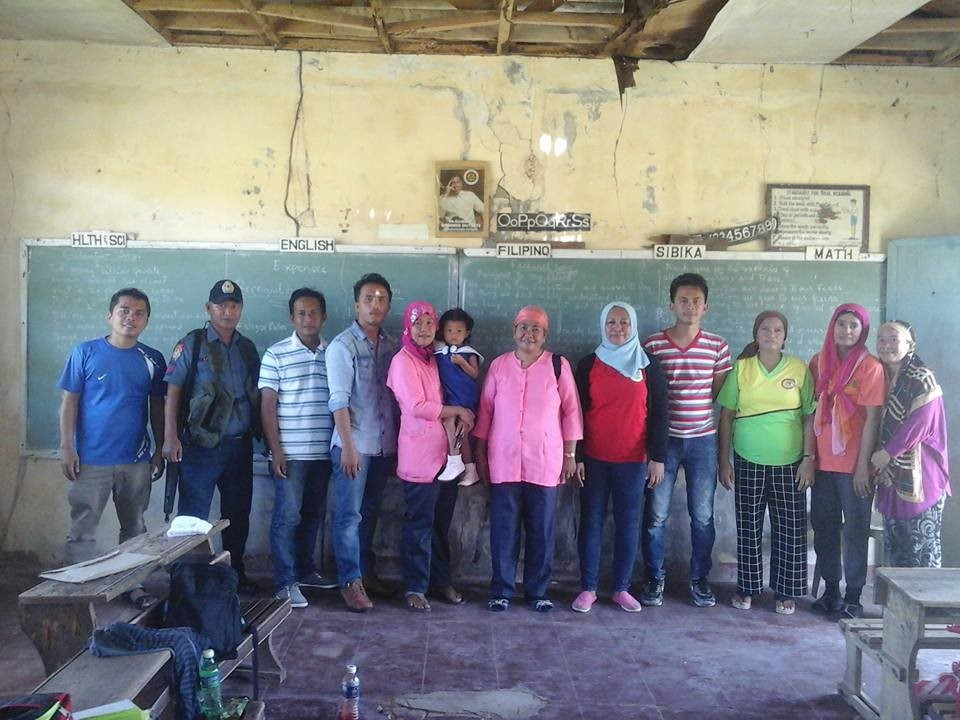 Field workers and security personnel pose with teachers inside a