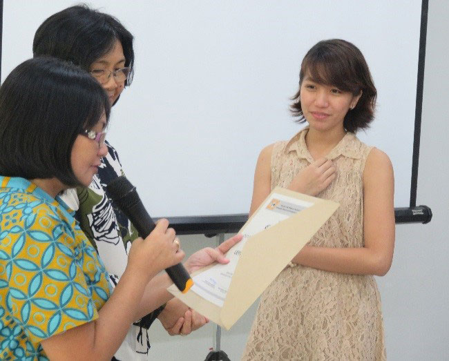 Prof. Maria Paz N. Marquez reads the certificate  as Prof. Grace T. Cruz (middle) and Ms. Musni look on
