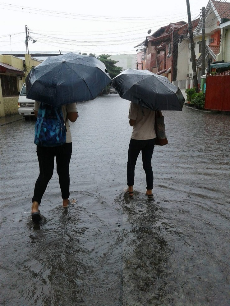 Field workers trod a flooded road to reach their target respondents [Olongapo City, Zambales; July 2018]