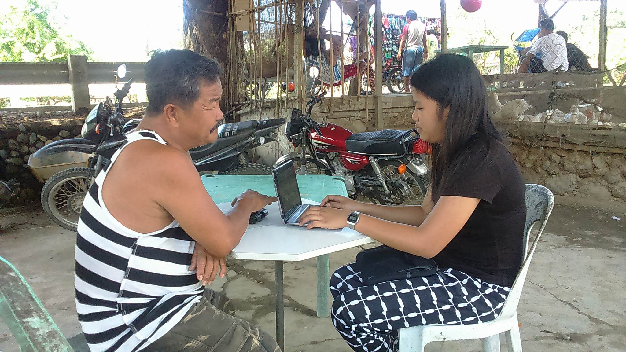 A female field worker interviews a male respondent using CAPI in a rural barangay in Ilocos Norte